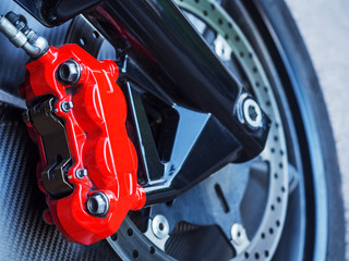 Roter Bremssattel an Bremsscheibe eines Motorrades