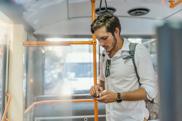 handsome young man using smartphone in bus