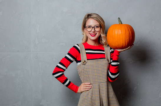 Portrait of a young style blonde girl in red striped sweater with halloween pumpkin on grey background.