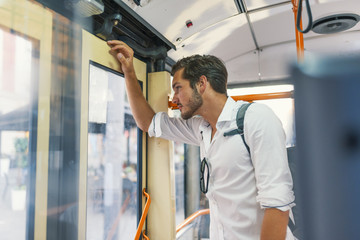 Businessman taking ride to work, standing inside train. Young man taking bus to work. Urban public transportation concept