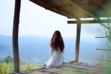 Young lonely woman sitting in cottage and looking view of nature, Relaxation on vacation trip