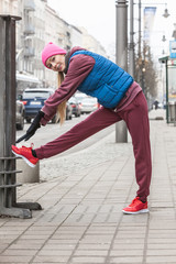 Sporty girl stretching outdoor on city street.