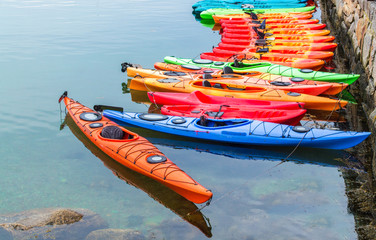 a row of colorful fiberglass kayaks for rent in a small Massachusetts harbor