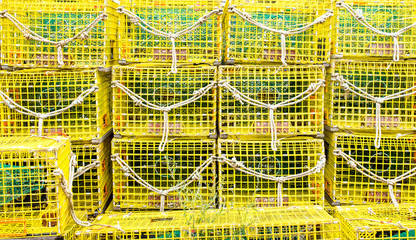 rows of bright yellow lobster traps with ropes attached stacked on a wharf in Massachusetts