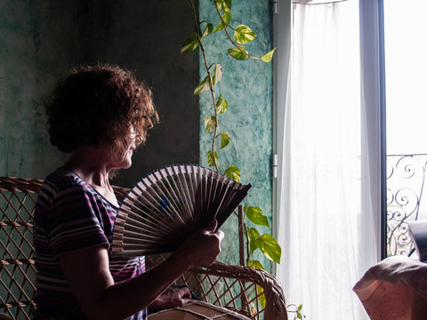 Portrait of mature woman with curly hair and eye glasses and spanish fan in a rural house looking through an open window