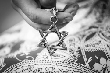 Young woman's hand holding a Star of David - Magen David key chain. The State of Israel, Holocaust remembrance, Judaism, Zionism concept image. Black and white image.