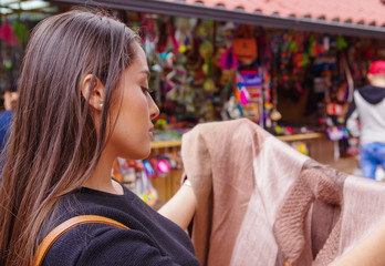 Close up of young woman holding in her hands a handmade at a craft store in the Passage Craft in the downtown of the city of Banos