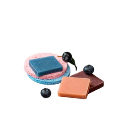 Pieces of natural handmade soaps and round cosmetic sponges on a white background.