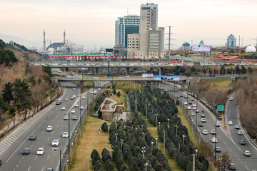 Islamic Republic of Iran. Tehran city center and mountainous background. Freeway with flags.