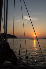Sunset through the rigging of a n old, wooden sailboatin the Andaman Sea of Thailand