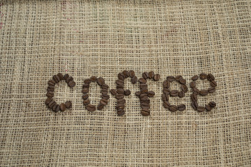 Coffee bean letters on a hessian background.