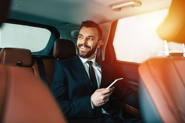 Handsome businessman with phone on hand sitting on the backseat of the car, guy looking away