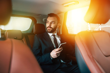 Confident bearded Businessman using mobile phone on back seat in car and looking away while trip