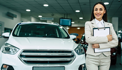 Beautiful smiling saleswoman in full suit in dealership on cars background with documents in tablet in hands