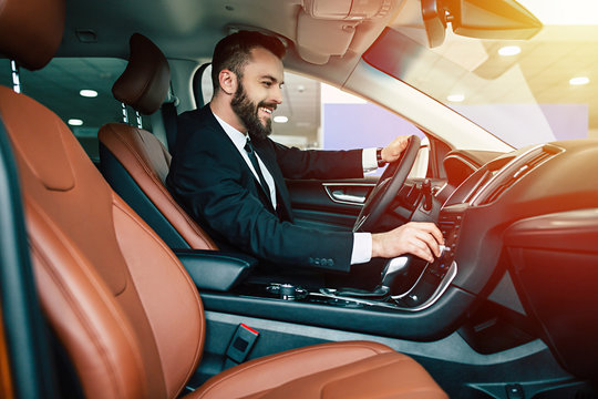 Attractive smiling elegant happy man in good car