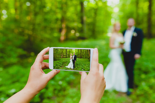 Somebody is using smartphone to make a photo of newlyweds