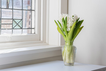 White hyacinths in glass vase on table next to vintage window (selective focus)