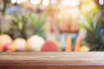 Wood table top on blurred with bokeh fruit in supper market background - can be used for display or montage your products.