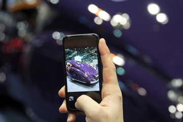 Man taking a picture a moder car at the auto show