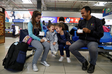 Venezuelan migrants Usleidy Pernalete, her children, Lucia Gomez, Daniel Gomez and brother Nelson Gil wait to be picked up after arriving from Zulia of Venezuela, during a five day trip, at the bus terminal in Lima