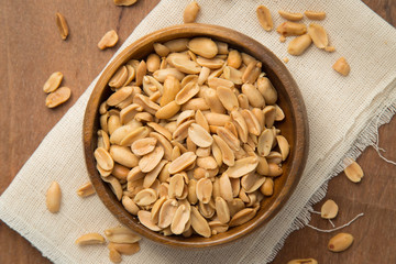 Roasted peanuts in wooden bowl putting on linen and wooden background.