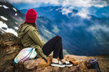 a woman sitting on the top of a mountain looking down at the forest valley below