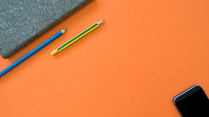 Wall Mural - Notebook with pencil and smartphone on orange background.Business concept copyspace