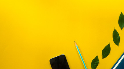 Wall Mural - Smartphone with pencil and leaves on yellow background business concept desk table copyspace
