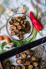 Roasted, grilled eggplants round slices with oregano herbs, spices baked on parchment paper in oven. Vegan vegetarian healthy lunch or dietary dinner.