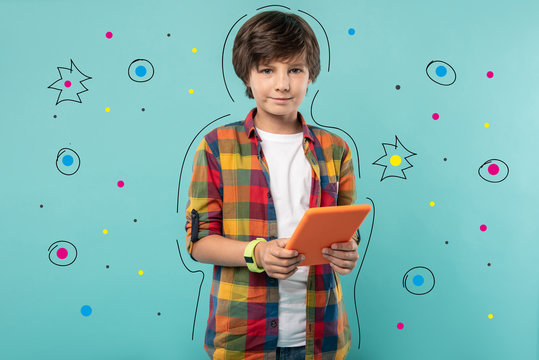 Modern tablet. Calm teenage boy looking glad and smiling while standing with his modern tablet after getting it for his birthday