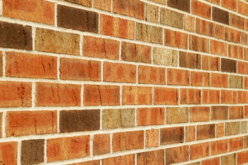 Angle view of a vintage brown multi-tone brick wall background with Flemish stretcher bond...