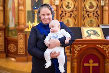 Belarus, Gomel, February 24, 2018. Church of the Birches.The baptism of a child.An old Russian grandmother in a scarf with an infant in a church at the altar