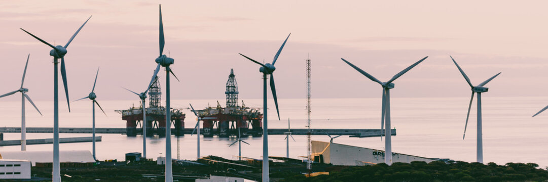 Group of windmills and solar panels for electric power production and oil rigs on coast.