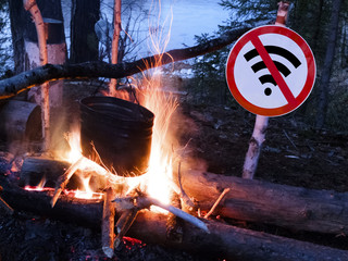 The no wifi sign near the fire and pot on the beach. digital detox concept and break from technology.