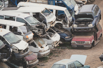 Car junkyard with many forgotten wrecks passenger cars.