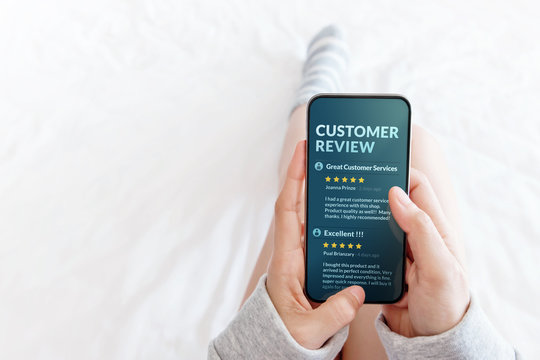Customer Experience Concept. Woman lying on Bed to Reading Online Review via Smartphone before Buying Products and Services, More Positive Feedback on Mobile Screen