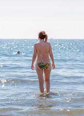 Young women enter in sunny warm sea near Cyprus Larnaca