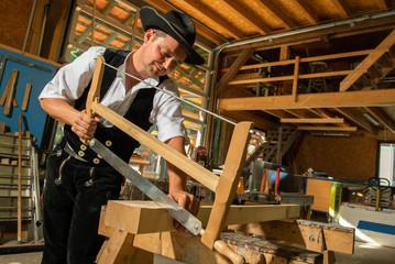 Zimmermann in traditioneller  Arbeitskleidung ,mit Schreiner Säge in der Werkstatt, sägen von Holzbalken
