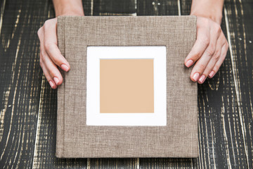 Top view photography of new brown modern photo book with empty frame for photo. White woman shows album isolated on wooden background. Horizontal color picture.