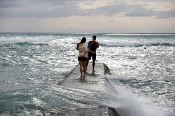 People take a photo on a sea wall in Waikiki Bay as Tropical Storm Lane approaches Honolulu