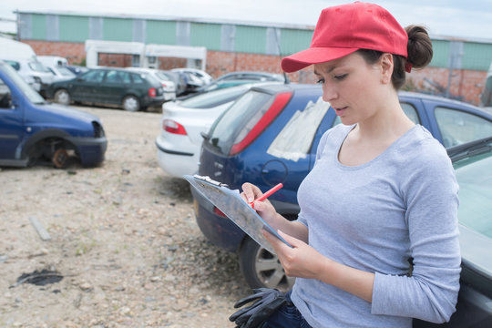 female working on car scrap yard