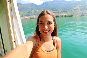 Selfie photo of young model woman on travel cruise vacation in orange tank top enjoying the evening on getaway holidays. Happy traveler vacations in Italy.