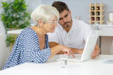 young man helping senior lady to use laptop