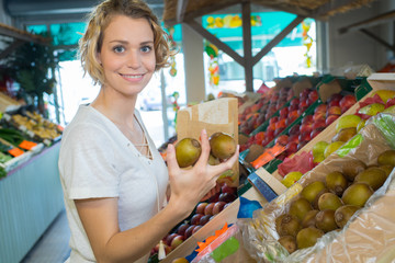 woman with bag buying apples at grocery store