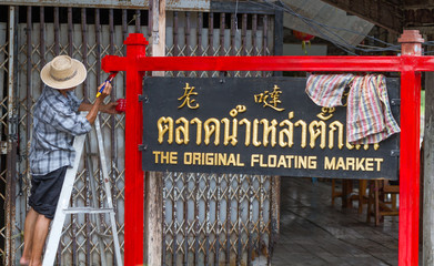 "Man painting sign ""The original floating market"", sign written in chinese, thai and english languages at Damnoen Saduak floating market in Thailand"