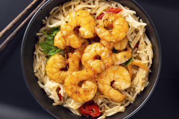Fried prawns and rice noodles with spices on a black plate. Black background. Eastern food. Copy space. Horizontal shot.