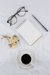 A cup of coffee, notebook, eyeglasses, pen and white flower bouquet on white bed