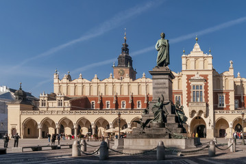 The Adam Mickiewicz statue and the Cloth Hall in the historic center of Krakow, Poland on a beautiful sunny day