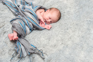 sleeping infant baby boy on a wrapped in a gray scarf on a gray furry bedspread