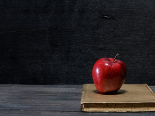 Red apple with book on wooden desk for back to school
